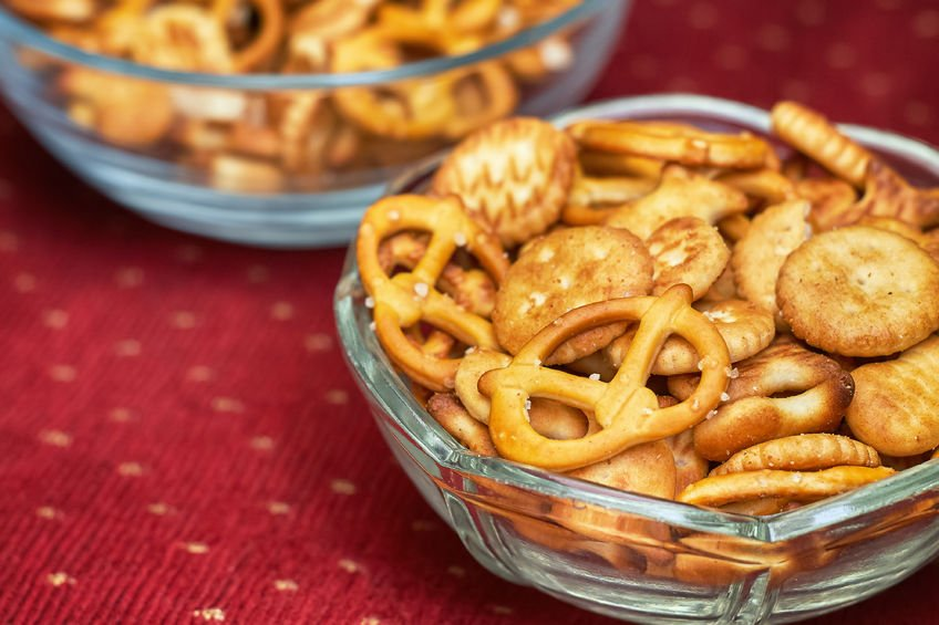 66037556 - mix of salty snacks (crackers and pretzels) in glass bowl on red background