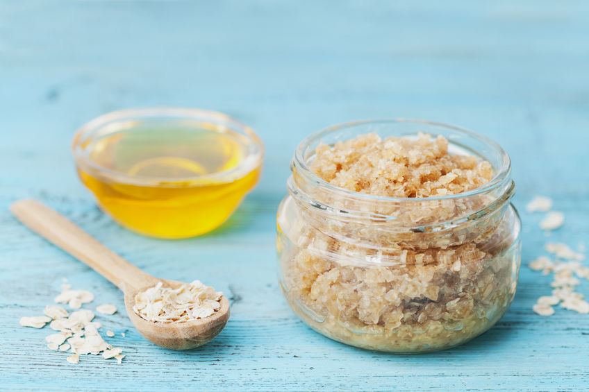 55848956 - body scrub of oatmeal, sugar, honey and oil in glass jar on blue rustic table, homemade cosmetic for peeling and spa care