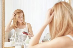 Young woman with thinning hair problem in front of mirror at home